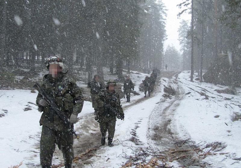Varusmiehiä kävelemässä kauniissa lumisessa Suomen keskikesässä
